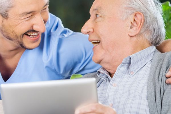 A close up of a doctor with his arm around an older man while they're both smiling and the older man is holding an iPad