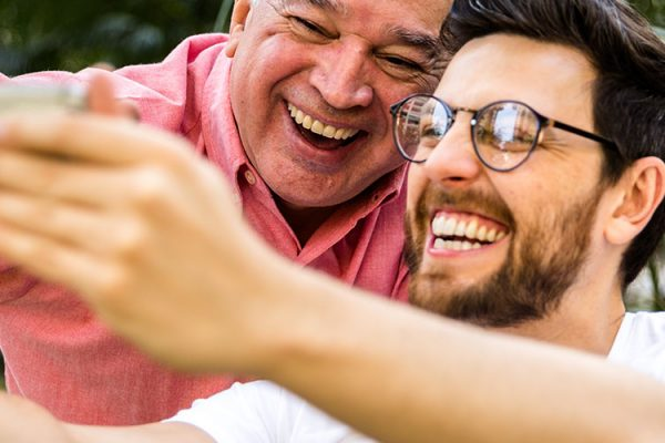 "An older man and young man with glasses are smiling and laughing while taking a ""selfie"" photo on a smartphone"
