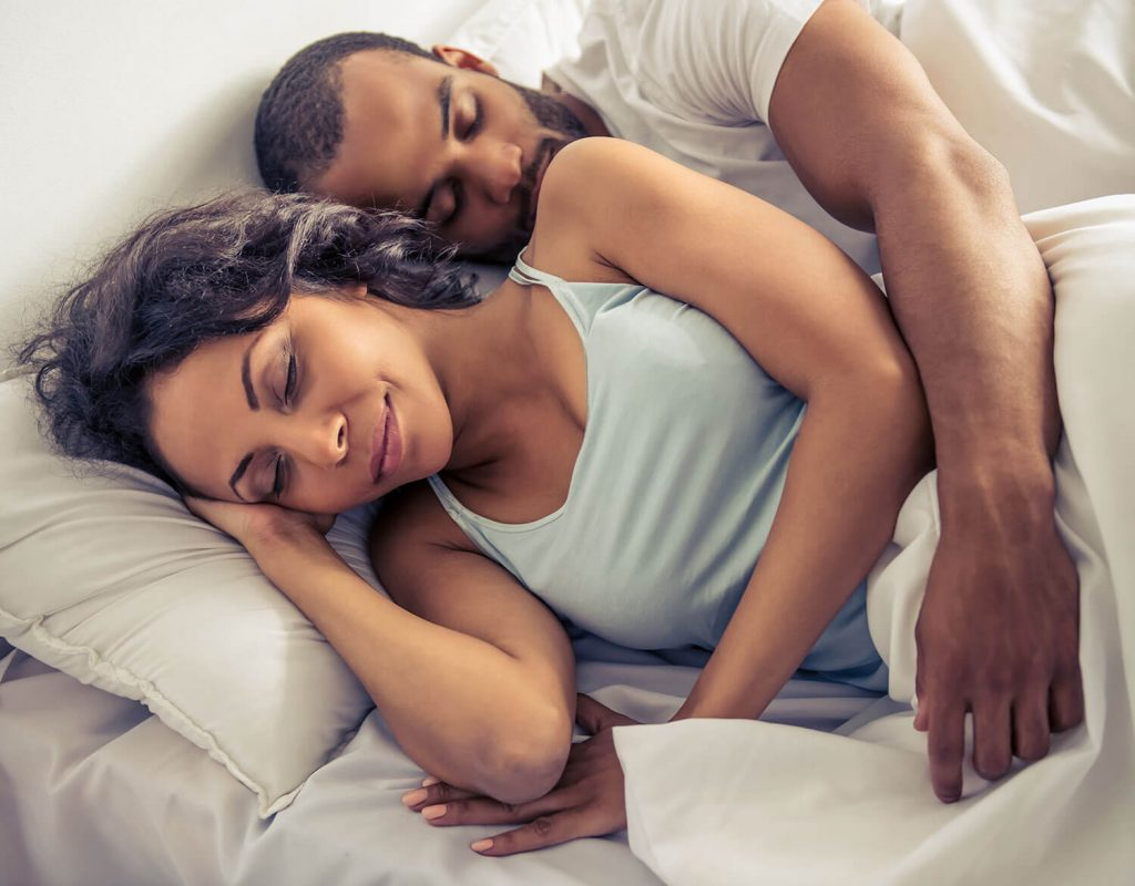 A couple sleeping soundly together in bed while man wraps his arm around the woman as she is smiling peacefully