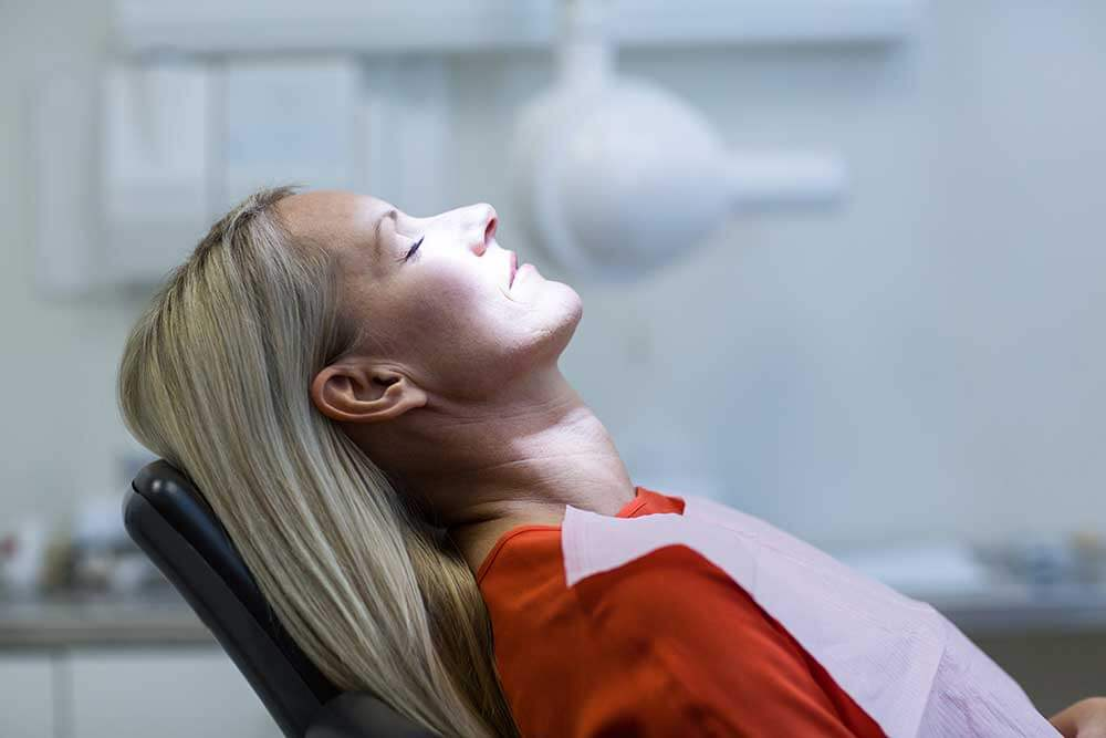Woman laying in a dentist chair with her eyes shut and the light shining on her as she prepares for treatment
